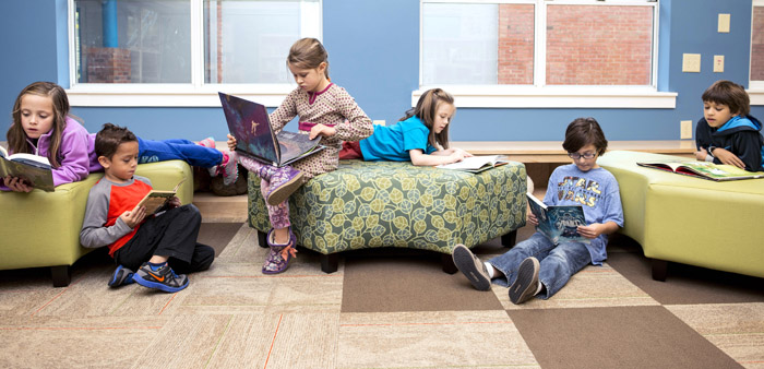 Students reading together on chairs and on the floor