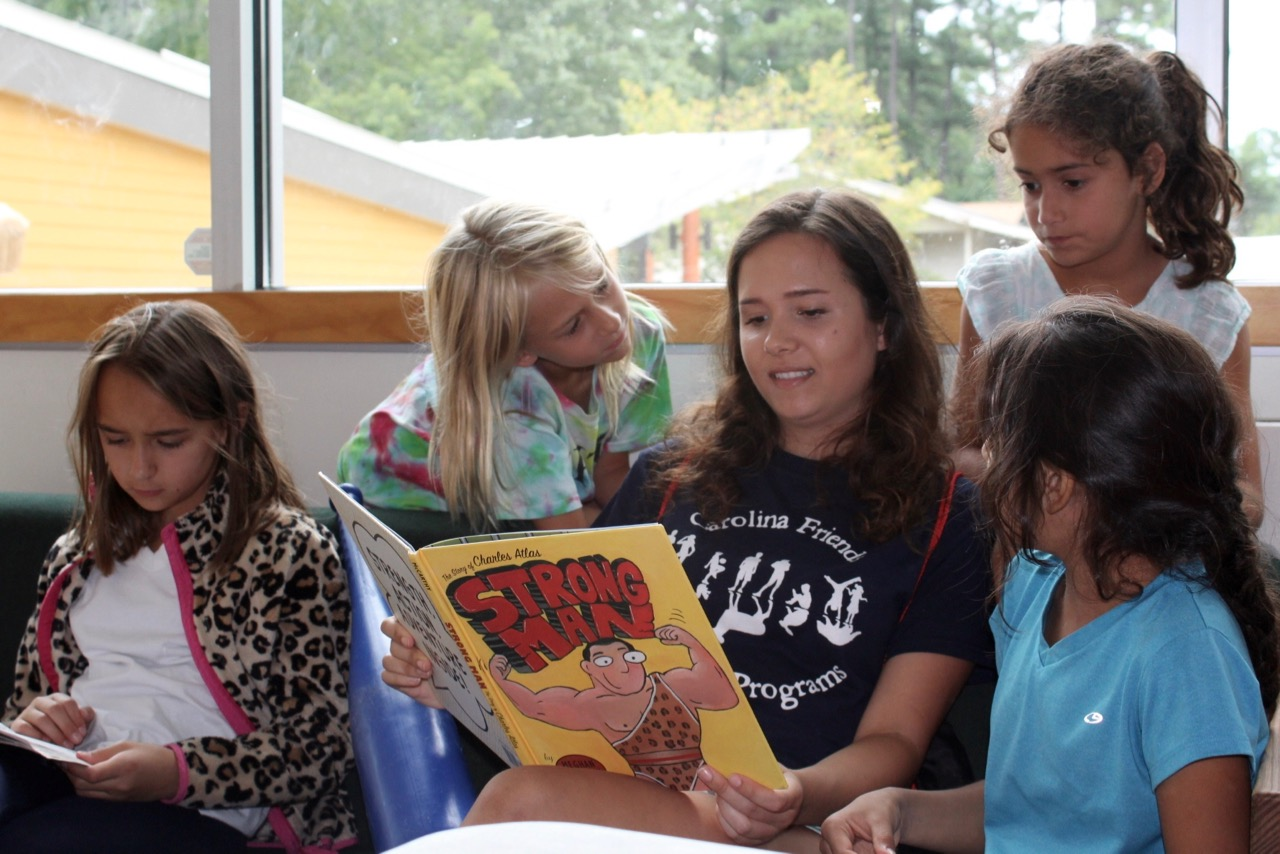 Group of students reading a book with counselor