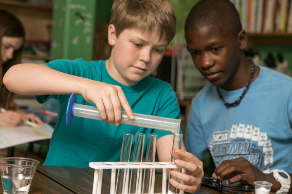 Two Middle School students conduct a chemistry experiment with test tubes