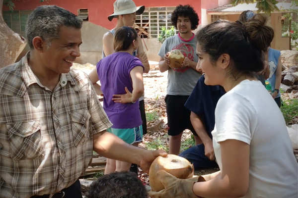 An Upper School student receives a coconut from a Cuban community partner on a service learning trip