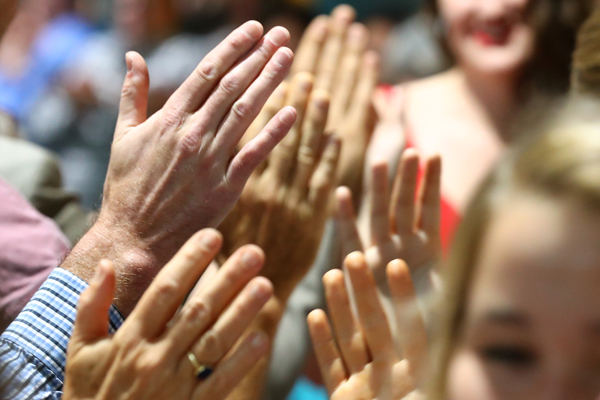 A group of hands reaching up for congratulatory high fives